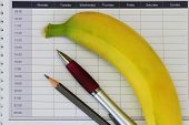 Pencil, pen and banana on open office agenda