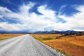 A dirt road in the endless pampas. Strong wind drives the clouds. On the horizon, the mountains visi