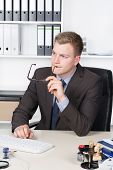 Young Businessman Is Thoughtfully Sitting At The Desk