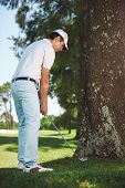 stock photo of disadvantage  - golfer in difficult situation behind tree in the rough a result of poor shot - JPG