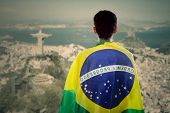 foto of backside  - Backside of young man with a Brazilian flag on his back looking at rio de janeiro city - JPG