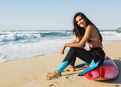 Beautiful surfist sitting over her surfboard