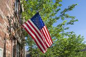 American Flag In Front Of A Brick Home