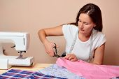 Young attractive woman cutting fabric on table