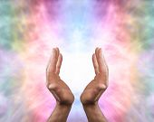 image of qi  - Male healer with outstretched hands and energy on an angelic rainbow colored energy background - JPG