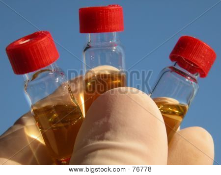 Picture or Photo of Hand showing three vials containing a golden liquid.