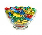 Candies wrapped in colored foil on white background