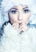Winter face close up of young attractive woman wearing hat and fur covered with snow flakes. Christmas beauty concept.