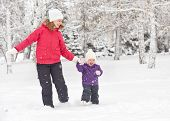 Happy Family Mother And Baby Girl Daughter Run, Walk And Playing In Winter Snow