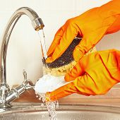 Hands in rubber gloves with sponge wash dirty plate under running water
