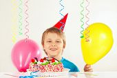 Young boy in holiday cap with festive cake and balloons
