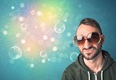 Young man with sunglasses and bokeh colourful lights concept