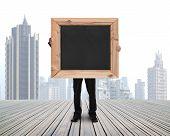 Businessman Holding Black Blank Chalkboard With Skyscraper Cityscape