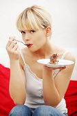 Portrait woman eating piece of cake.