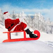 Santa Claus on sledge with blur snowy background