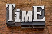 time word in vintage metal type printing blocks over grunge wood