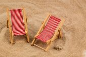 a small deck chair (model) on a sandy beach. photo icon for vacation, holiday, travel