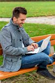 a man with a laptop sitting on a park bench