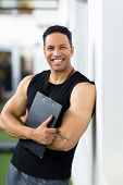 smiling male trainer with clipboard standing in gym