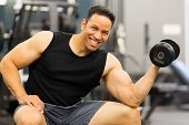 happy middle aged muscular man holding dumbbell in gym
