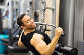 handsome mid age man doing pull-down workout in gym