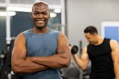 fit young african man posing with arms folded in gym