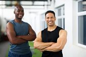 cheerful male athletes with arms crossed in gym