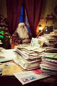 image of letters to santa claus  - Messy Santa Claus desk with lots of letters he is sitting on the background - JPG