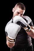 image of kickboxing  - a young kickboxer or boxer isolated over a black background
