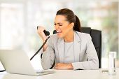 angry young businesswoman screaming at telephone in office