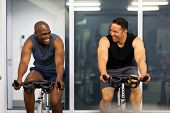 cheerful men working out in gym