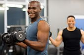 stock photo of dumbbell  - healthy african man working out with dumbbells in gym - JPG