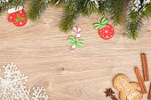 Christmas fir tree, gingerbread cookie and decor on wooden background