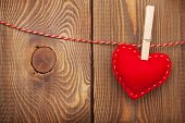Red toy valentines heart on rope over wooden background with copy space
