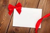 Valentines day greeting card with red ribbon over wooden background