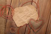 Blank old piece of paper and vintage handmaded valentines day toy heart over wooden background