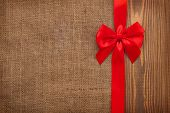 Valentines day background with red ribbon over wood and burlap
