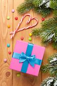 Gift box over christmas wooden background with snow fir tree and candies