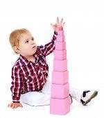 picture of montessori school  - Little boy builds a pyramid in the Montessori school - JPG