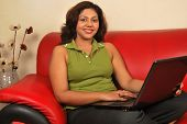 young indian woman with laptop working from home