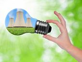 Hand holding bulb with nuclear power plant on green background