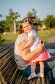 Baby girl standing on a bench hugging to woman