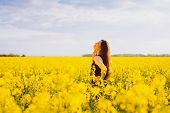 Side view of young woman with long hair touching her neck on yellow blooming rapeseed field