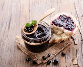 Delicious black currant jam on table close-up