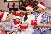 Festive family in santa hat exchanging gifts at home in the living room
