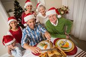 Father in santa hat carving chicken during christmas dinner at home in the living room