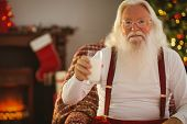 Cheerful santa holding a glass of milk at home in the living room