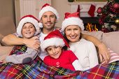 Festive family hugging under the cover at home in the living room