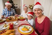 Happy family in santa hat during christmas dinner at home in the living room