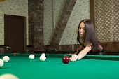 sexy girl in corset plays billiards.